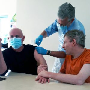Gary holds Rob's hand as he gets the COVID-19 vaccine